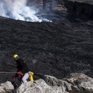 a member of Miles Beyond rappelling the crater of Niyragongo volcano