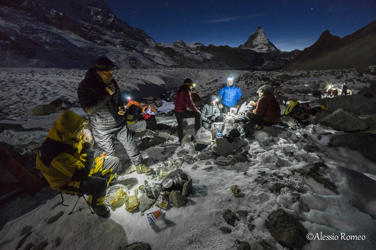 The picture shows the participants to the expedition having the dinner in the base camp, outside the tents, during the cold night of the Corner glacier