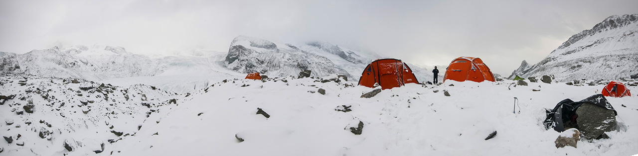 The picture shows the base camp over the Corner glacier. Red tents in the snow